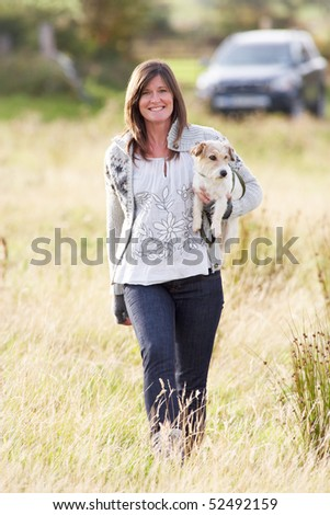 Young Woman Outdoors In Autumn Landscape Holding Dog - stock photo