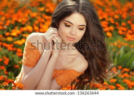 Young woman outdoors portrait over orange marigold flowers - stock photo