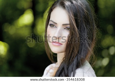 Young woman outdoors portrait.Young beautiful woman, on green background summer nature. Beautiful sexy brunette outdoors.Attractive Brunette Girl. Eyes beautiful woman. - stock photo