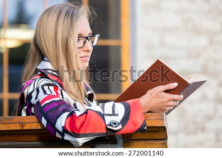 Young woman outdoors sitting on the bench and reading a book, with eyeglasses, dressed in colorful coat. - stock photo