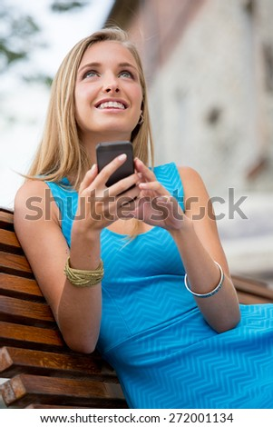 Young woman outdoors sitting on the bench, holding her mobile phone, texting and smiling, dressed in blue dress. - stock photo