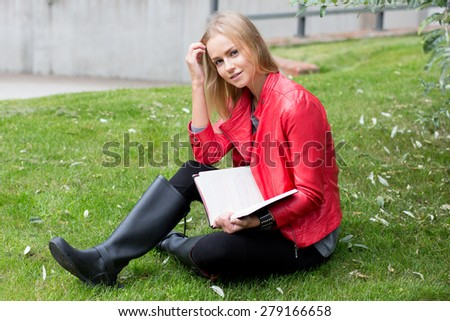 Young woman outdoors sitting on the grass and reading a book. - stock photo