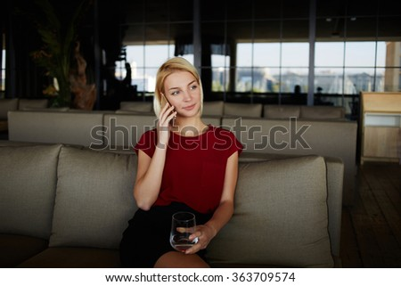 Young woman owner calling with cell telephone while waiting to the meeting with designer, beautiful female restaurateur holding glass of fresh water and phoning via mobile phone while sitting in cafe - stock photo