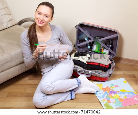 Young woman packing a suitcase at home going on holiday - stock photo