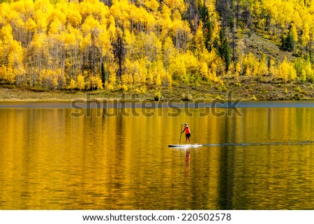 Young woman paddle boarding on mountain lake on warm fall day with yellow Aspen trees reflecting in water - stock photo