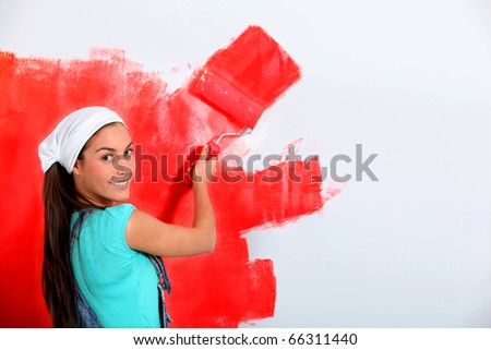 Young woman painting house wall in red - stock photo