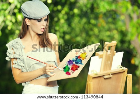Young woman painting landscape in the open air - stock photo
