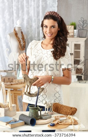 Young woman painting wooden horse, enjoying hobby at retro home. - stock photo