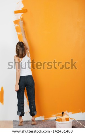 Young woman paints her walls orange with a roller - stock photo