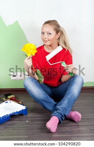 Young woman paints interior wall of home