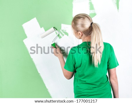 Young woman paints the wall, full length portrait