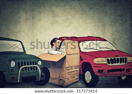 Young woman parking her compact car in between large SUV gas guzzlers  - stock photo