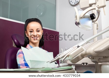 Young woman patient in checkered shirt with perfect straight white teeth waiting for dentist in dental chair and smiling relaxed, ready for a check-up. Beautiful girl smile - stock photo