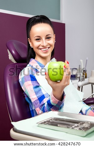 Young woman patient with perfect straight white teeth waiting for dentist in dental chair and smiling with green apple in hand. Beautiful girl smile - stock photo