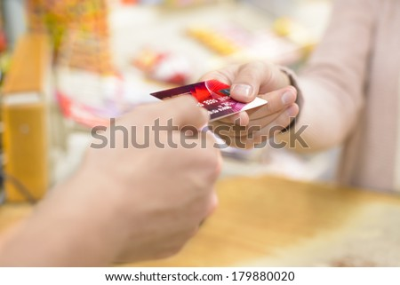Young woman paying in a shop