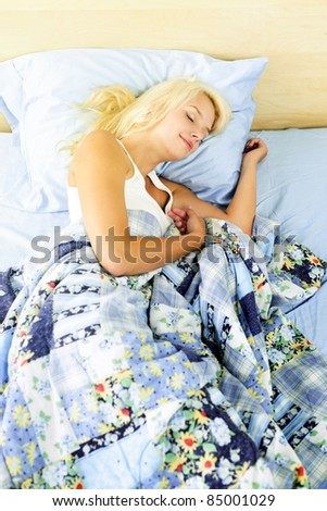 Young woman peacefully asleep in bed in the morning