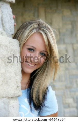 young woman peeking out from behind wall - stock photo