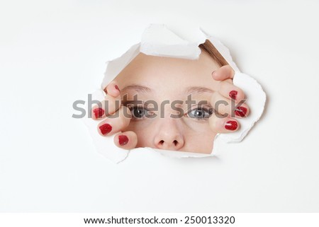 young woman peeking through hole in paper wall  - stock photo