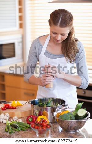 Young woman peppering her meal