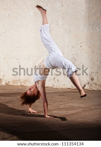 Young woman performing a cartwheel on floor - stock photo