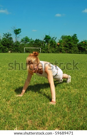 Young woman performing push-up or press-up exercise on soccer field.