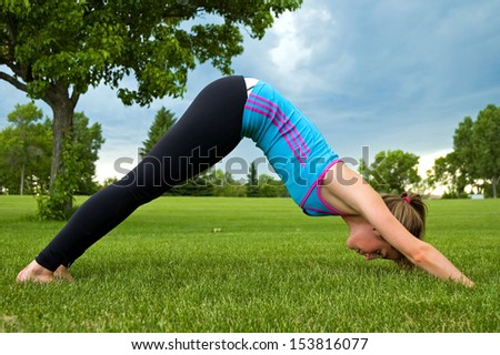 Young woman performing the Down Dog yoga pose, in a park.