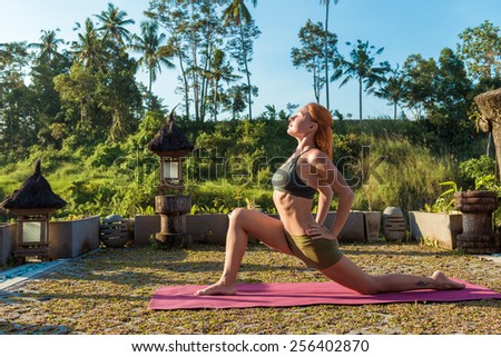 Young woman performing yoga asana at sunset with jungle background - stock photo