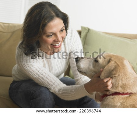 Young woman petting her dog - stock photo