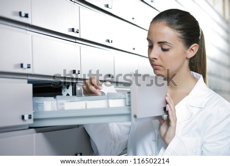 Young woman pharmacist taking medicine from drawer