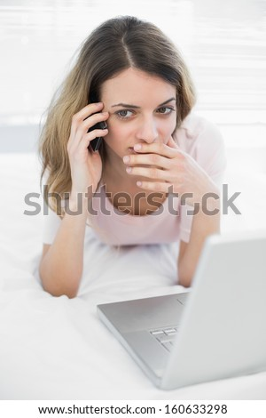 Young woman phoning with smartphone lying on her bed in front of her notebook