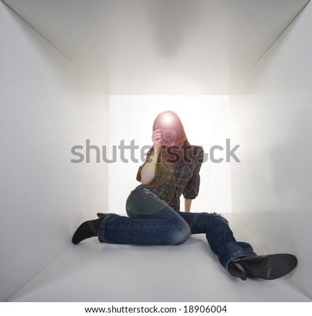 Young woman photographer in a white box taking photo with flash