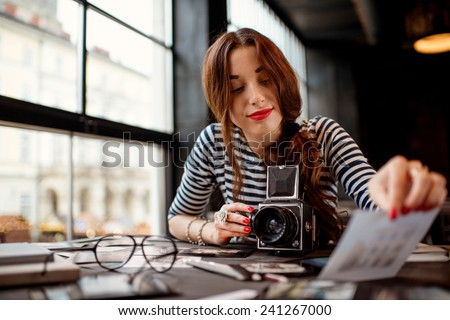 Young woman photographer looking at the printed photos with old 6x6 frame camera sitting in the cafe with loft design interior - stock photo