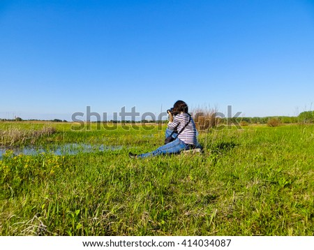 young woman photographer taking photo of the landscape