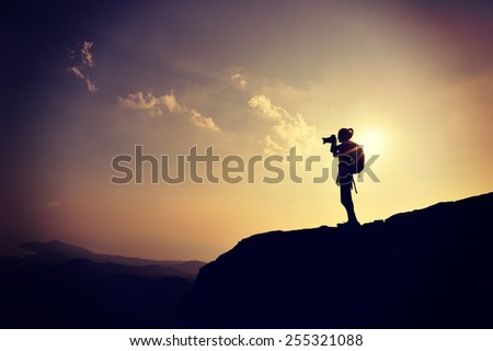 young woman photographer taking photo on sunset mountain peak - stock photo