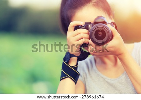 young woman photographer taking photo outdoor - stock photo