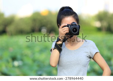 young woman photographer taking photo outdoor