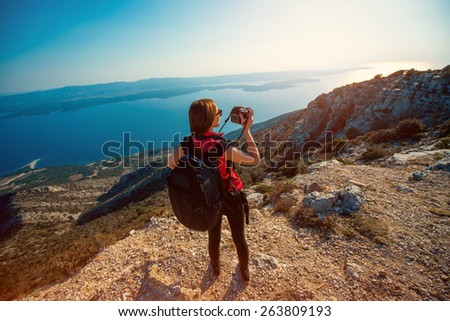 Young woman photographer with backpack photographing sunset on the top of island mountain