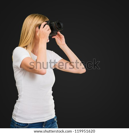 Young Woman Photographing against a black background