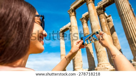 Young woman photographing with smart phone Zeus temple in Greece - stock photo