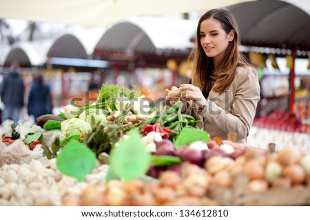Young woman picking fresh produce at the market - stock photo