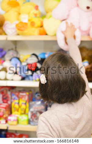 Young woman picking toys in a store - stock photo