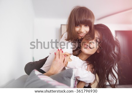 Young woman piggybacking her joyful little daughther at home in white lit room against the window. Smooth morning light, casual style - concept of happy family living and lifestyle - stock photo