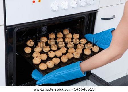 Young Woman Placing Tray Full Of Cookies In Oven