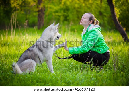 young woman play with husky in the park