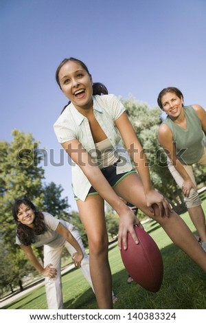 Young woman playing American football with two female friends in the park - stock photo