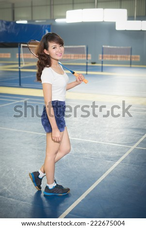 Young woman playing badminton in Gym