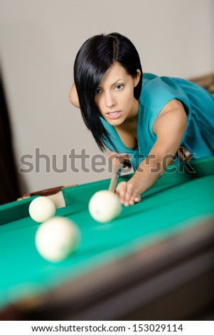 Young woman playing billiard. Spending free time on gambling - stock photo