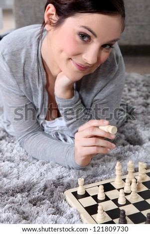 Young woman playing chess - stock photo