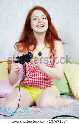 Young woman playing computer games on the bed at home - stock photo