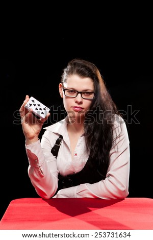 Young woman playing in the gambling on black background - stock photo